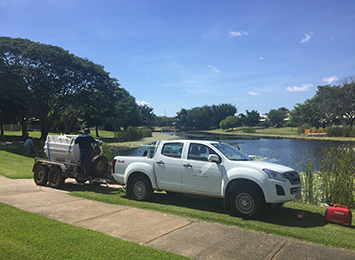 A utility vehicle with a trailer parked in front of a lake, and a Northern Territory Government employee with his back to the camera