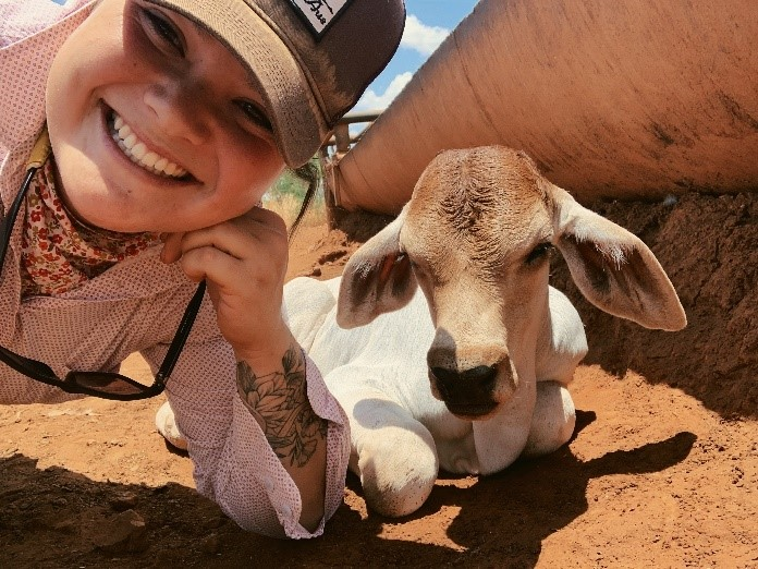 NT DPIR Technical Officer Elle Fordyce with a calf at the water trough